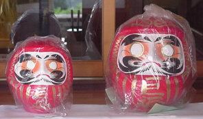 Daruma tumbler dolls, still in their protective plastic wrapping